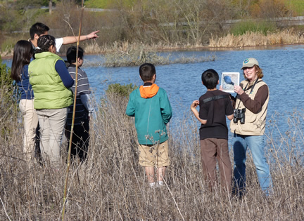 Docent hold up photo during bird-watching exercise for middle-school children sloughside