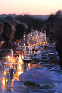 Diners at table a few minutes after sunset, lit with candles