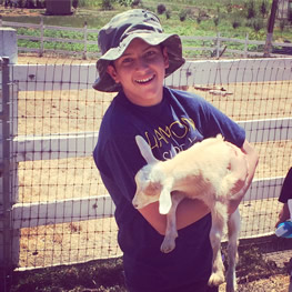 Green Careers intern Daniel with baby goat at Lonely Mountain Farm